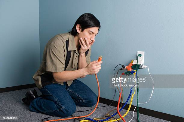 Confused man with power cords