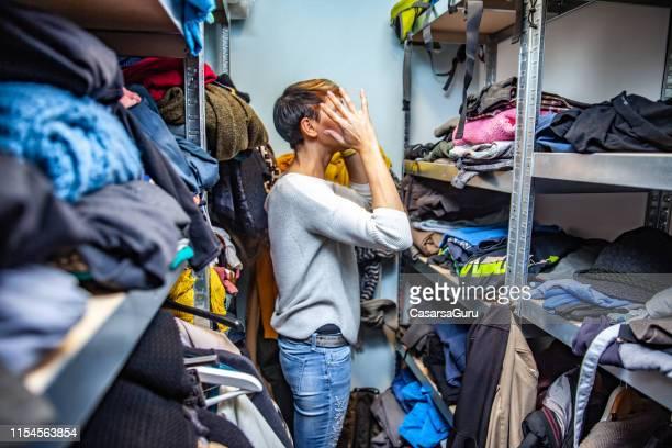 verwarde moeder op zoek naar kleding. - keurig stockfoto's en -beelden
