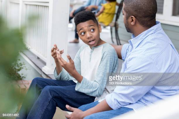 confused preteen son talks to father on front porch - penalty stock pictures, royalty-free photos & images