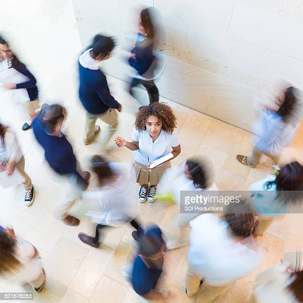 Confused private school student standing in busy crowd of classmates