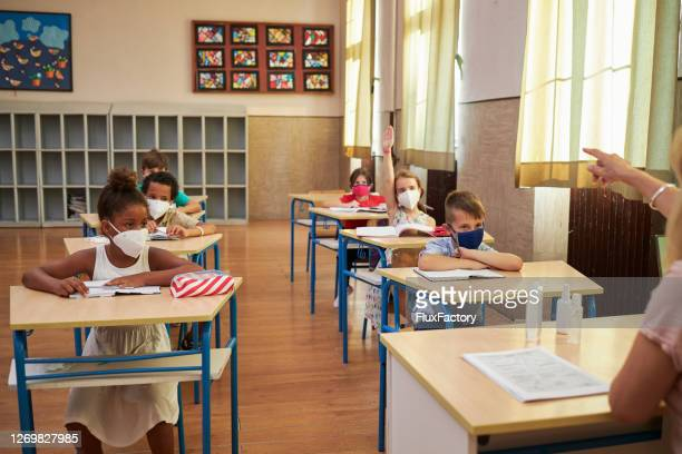confused school girl raising her hand to ask a question during teacher lecture - reopening stock pictures, royalty-free photos & images