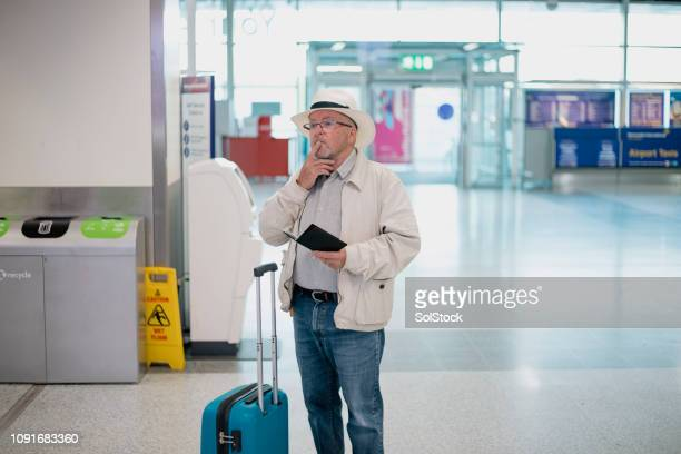 confused senior man at airport - lost stock pictures, royalty-free photos & images