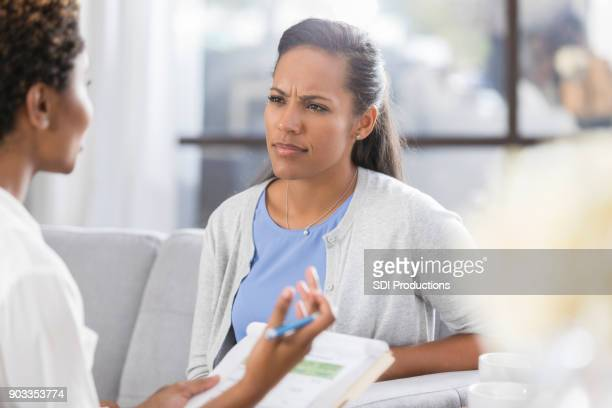 confused woman listens to counselor - negative emotion stock pictures, royalty-free photos & images