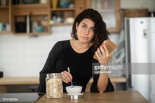 confused woman sitting at kitchen counter eating breakfast while looking at her mobile phone - confusão imagens e fotografias de stock