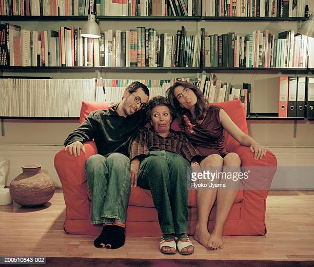 Confused woman sitting between couple making faces on red sofa at home
