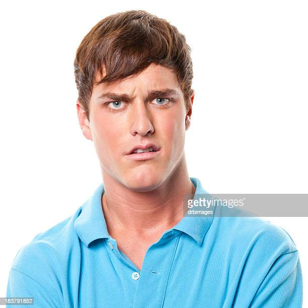 confused young man frowning - uncomfortable stock pictures, royalty-free photos & images