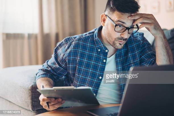 confused young man working at home - struggle stock pictures, royalty-free photos & images