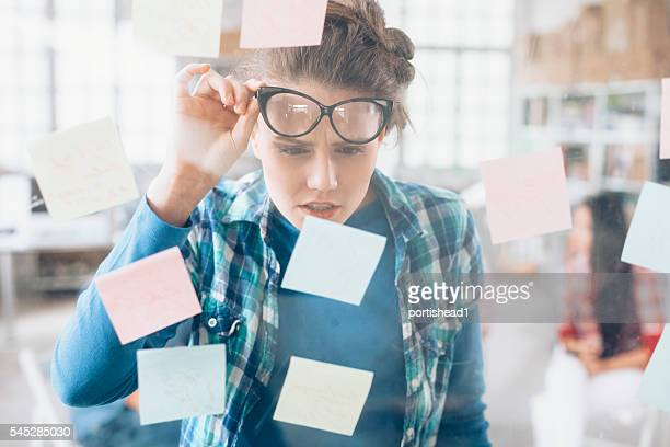 Confused young woman trying to read sticky notes