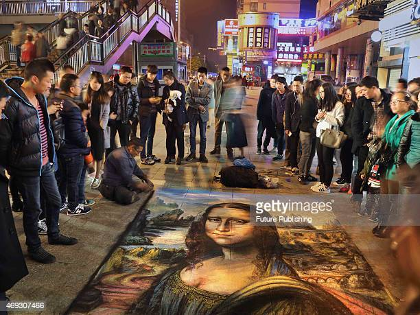 Cong Langui creates a sixsquaremeter masterpiece 'The Mona Lisa' by chalk on the streets of Jinhua on April 10 2015 in Zhejiang East China Cong lost...