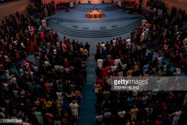 TOPSHOT Congergants attending Sunday service at the House On The House Church in Lagos rise as Senior Pastor Paul Adefarasin starts his sermon in...
