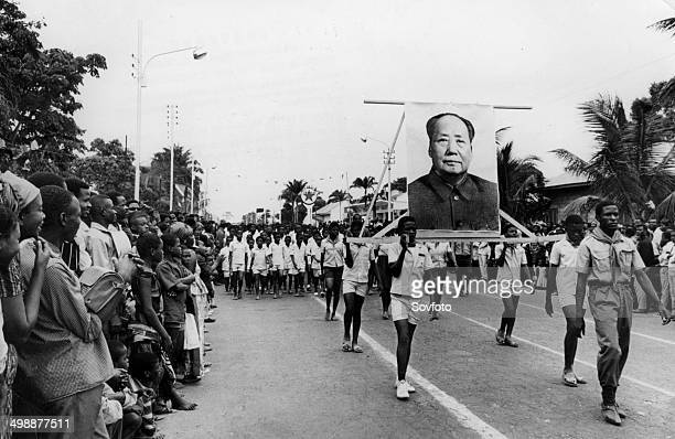 Congo youth carrying a large portrait of Mao Tsetung ina parade honoring the 2nd anniversary of the August Revolution 1965