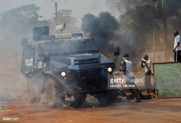 A Congolese armored vehicle of the UPC Congo drives a blackboard reading Frence war crime against RCA during a protest against the French Sangaris...