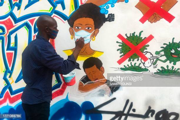 Congolese artist Chris Shongo paints on the outside wall of the Academie des Beaux-Arts in Kinshasa on June 18, 2020. - Several students from The...