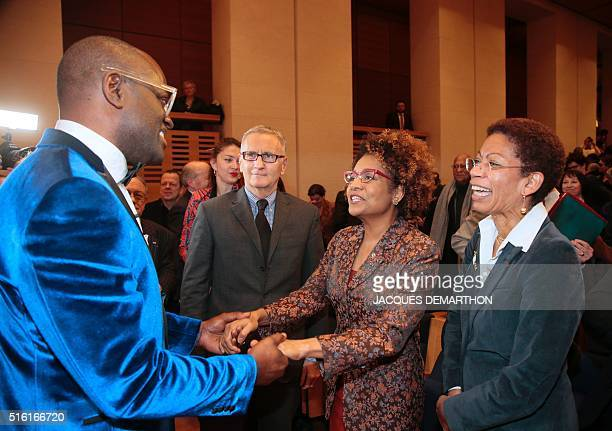 Congolese author Alain Mabanckou holds the hands of Canadian SecretaryGeneral of the International Organisation of La Francophonie Michaelle Jean as...