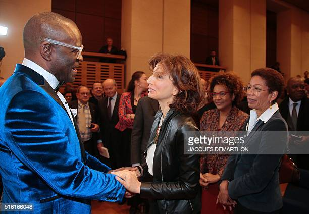 Congolese author Alain Mabanckou holds the hands of French Culture minister Audrey Azoulay as Canadian SecretaryGeneral of the International...
