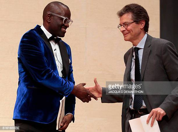 Congolese author Alain Mabanckou shakes hands with Antoine Compagnon literature professor at the College de France on March 17 2016 at the College de...