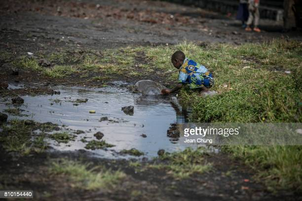 Congolese boy plays with water in a puddle right outside Mugunga III IDP camp on June 8 2014 in Mugunga Democratic Republic of Congo Congolese in the...
