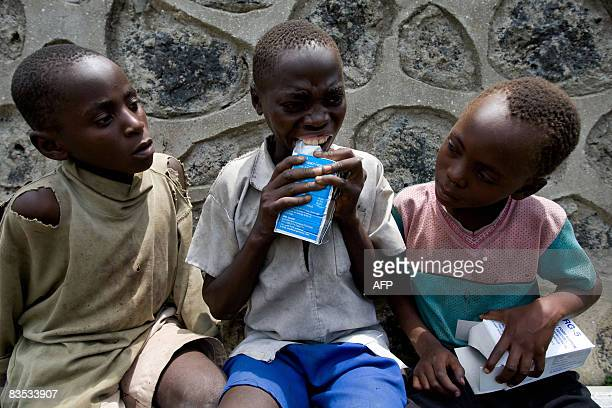 Congolese children open a package containing high nutrition cookies at the Mercy Corps office where UNICEF and IMC were distributing High nutrition...