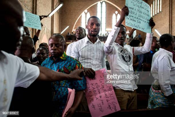 Congolese display posters at a Catholic service to commemorate the victims of a crackdown on last month's march on January 12 2018 in Kinshasa Police...