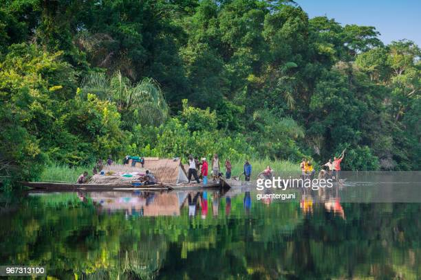 congolese families travelling by boat on congo river - democratic republic of the congo stock photos and pictures