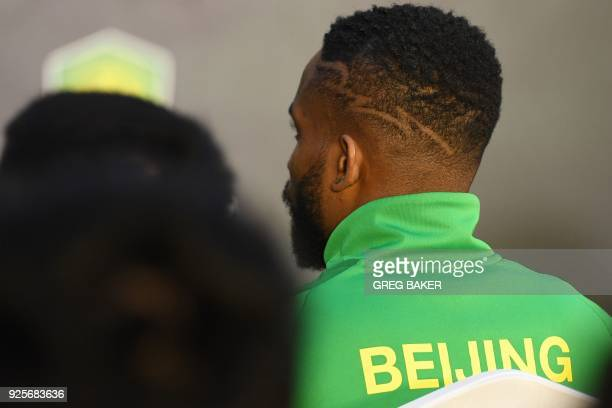 Congolese football player Cedric Bakambu sits at a press conference held by his new team Beijing Guoan in Beijing on March 1 2018 Chinese Super...