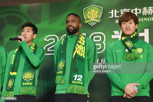 Congolese football player Cedric Bakambu stands with new teammates at a press conference held by his new team Beijing Guoan in Beijing on March 1...
