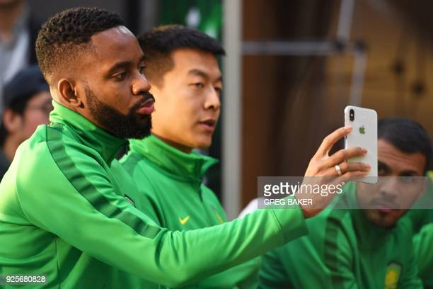 Congolese football player Cedric Bakambu takes a selfie during a press conference held by his new team Beijing Guoan in Beijing on March 1 2018...