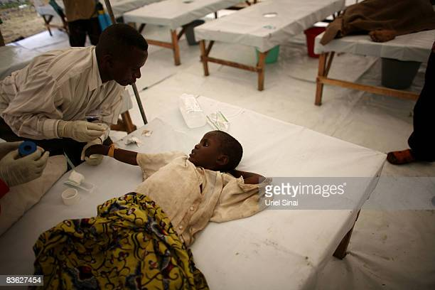 A Congolese girl is treated for cholera in an Medecins Sans Frontieres tent clinic at the Kibati refugee camp November 10 2008 just outside the town...