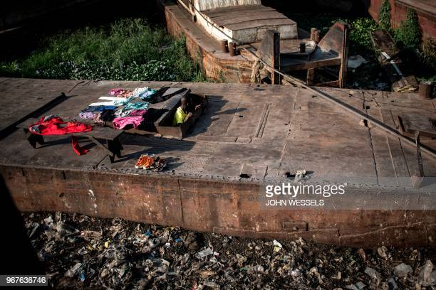 Congolese man climbs out of the hull of a disused barge which is used as a makeshift home along the banks of the Congo River on June 4, 2018 in...