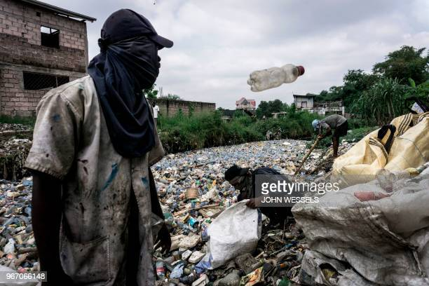 TOPSHOT Congolese men collect plastic bottles on the edge of the Kalamu River on May 31 2018 in Kinshasa On June 5 2018 the United Nations mark the...