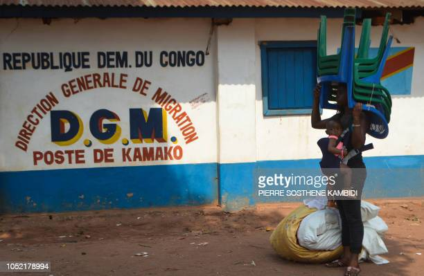 Congolese migrant who was living in Angola holds a child in the Congolese border town of Kamako on October 12 after returning to her country...