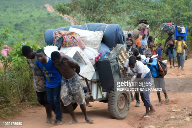 Congolese migrants who were living in Angola carry belongings near the Congolese border town of Kamako on October 12 after returning to their country...