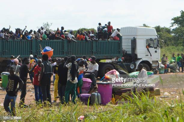 Congolese migrants who were living in Angola stand in truck as they leave the Congolese border town of Kamako on October 12 after returning to their...