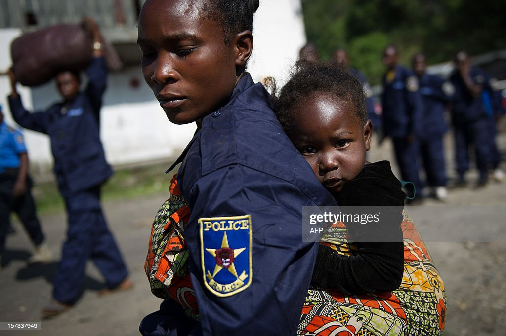 A Congolese national police officer carries her child after disembarking from a boat at the port in the city of Goma, in the east of the Democratic Republic of Congo, on December 2, 2012. After M23 rebels pulled out of Goma yesterday, 166 government police officers arrived this morning from Bukavu.
