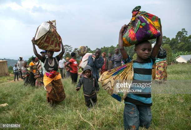 Congolese people carry their belongings after they crossed the border from the Democratic Republic of Congo to be refugees at Nteko village in...