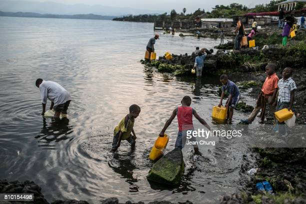 Congolese people fetch water from the Kivu Lake and carry the water containers back home on June 5 2014 in Goma Democratic Republic of Congo...