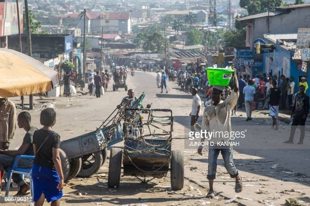 Congolese people walk as streets remain quiet despite a call by the main opposition, the Union for Democracy and Social Progress to hold anti...