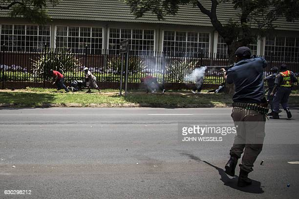 TOPSHOT Congolese protesters scatter as police fire rubber bullets whilst they protest outside the Democratic Republic of the Congo's Embassy in...