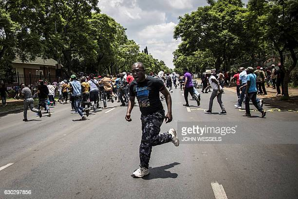 TOPSHOT Congolese protesters scatter as police open fire with rubber bullets whilst they protest outside the Democratic Republic of the Congo's...