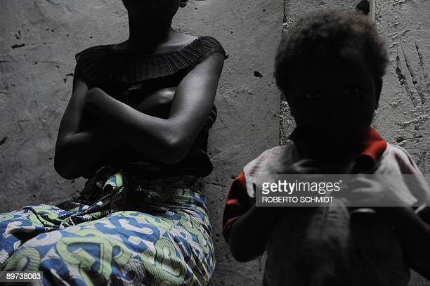 A Congolese rape victim crosses her arms while sitting next to an infant in front of the transit house they stay in at the Heal Africa clinic in Goma...