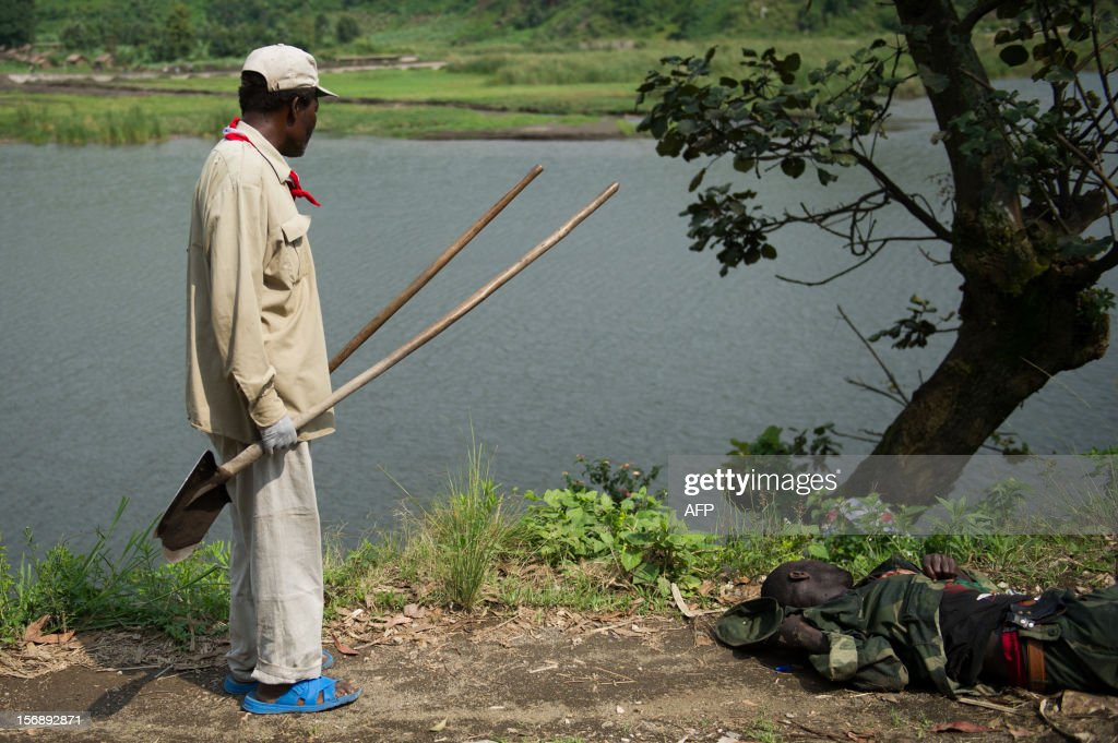 A Congolese Red Cross volunteer stands beside the corpse of a government army soldier left lying on the roadside near Sake in the east of the Democratic Republic of the Congo on November 24, 2012. The Red Cross were working around Sake today, clearing the bodies left from fighting on Thursday as M23 rebels clashed with the government army.
