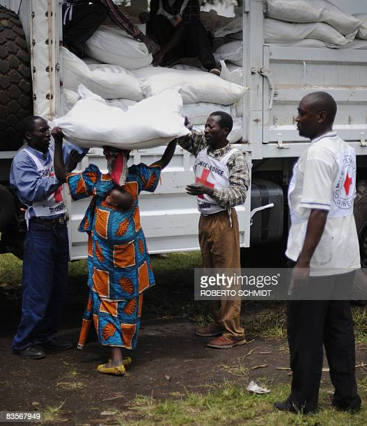 Congolese Red Cross workers place a 60 kilo bag of maize flour on a woman's head as thousands of Internally Displaced People received food aid from...