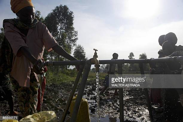 Congolese refugee fills a jerry can with water at a water supply tap located in the Kibati camp for refugees just north of the provinicial captial of...