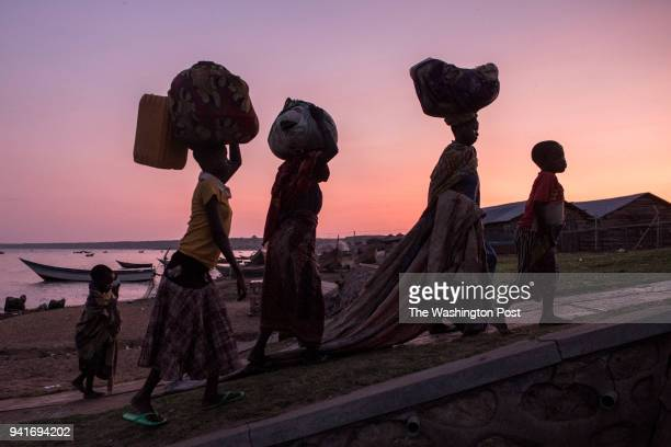 Congolese refugees exit a boat after landing in Sebagoro Uganda on March 24 2018 Violence in Ituri Province in northeastern Democratic Republic of...