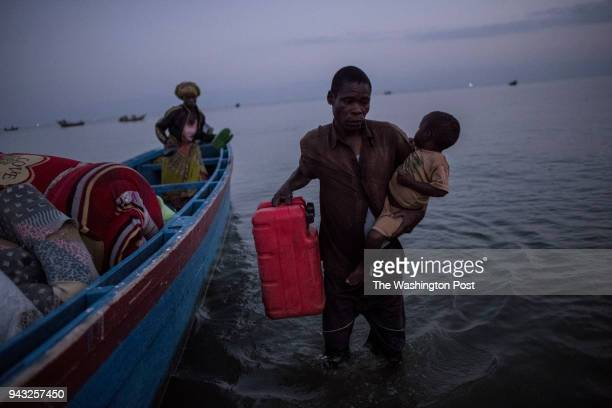 Congolese refugees exit a boat after landing in Sebagoro Uganda on March 23 2018 Violence in Ituri Province in northeastern Democratic Republic of...