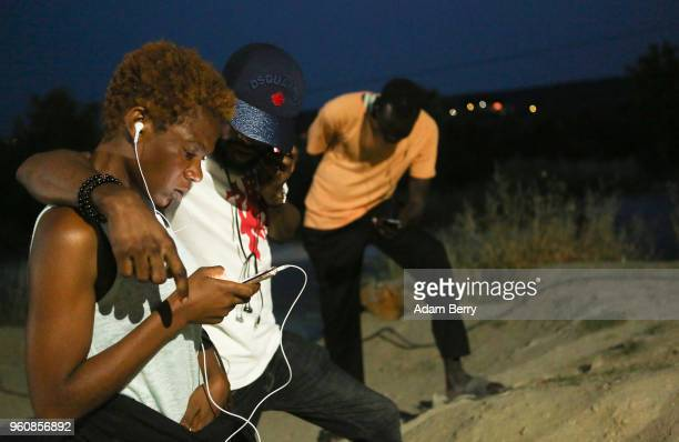 Congolese refugees use one of the few available WiFi hotspots to communicate with family members at the Moria refugee camp on May 20 2018 in Mytilene...