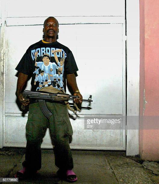 Congolese soldier wearing a Maradona tshirt and carrying an AKM assault rifle keeps watch 09 May 2005 at the residence of a Congolese Army Colonel at...