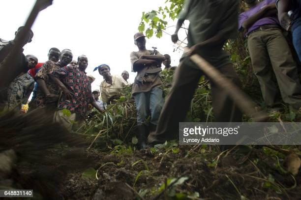 Congolese villagers and soldiers with the Rwandanled Hutu militia known as the Democratic Liberation Forces of Rwanda FDLR stand over a mass grave in...