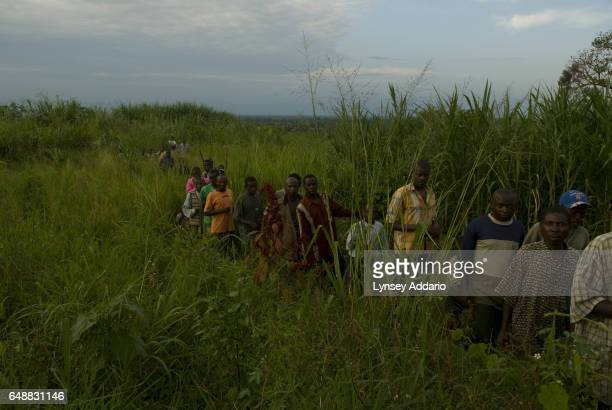 Congolese villagers and soldiers with the Rwandanled Hutu militia known as the Democratic Liberation Forces of Rwanda FDLR leave the site of a mass...