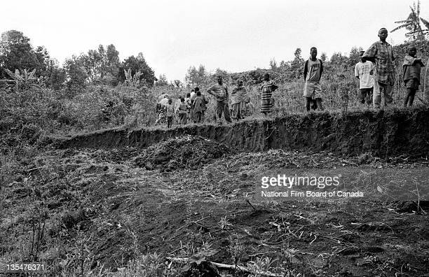 Congolese villagers gather next to a mass grave outside of the village of Drodro, where many people have been buried after it was attacked in April...